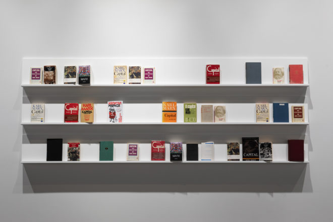 "Stephanie Syjuco, Excess Capital (Double or Nothing), 2013–, Used copies of Karl Marx's ""Capital,"" three shelves stacked vertically. Books, variable dimensions; Shelves, 120 x 12 inches, each. Courtesy of the artist. Photo: Henrik Kam"