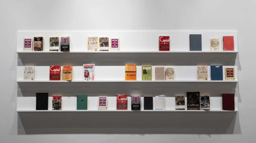 """Stephanie Syjuco, Excess Capital (Double or Nothing), 2013–, Used copies of Karl Marx's """"Capital,"""" three shelves stacked vertically. Books, variable dimensions; Shelves, 120 x 12 inches, each. Courtesy of the artist. Photo: Henrik Kam"""